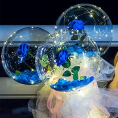 With string lights 3 Blue roses inside 3 transparent balloon with White and Blue Wrapping