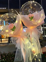 2 Pink Roses rose inside 2 transparent balloon with red and White Wrapping with fairy light