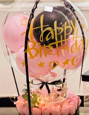 Happy birthday print on the transparent balloon with small pink and black balloons stuffed inside in a box of 20 pink roses beads string and string lights black ribbons