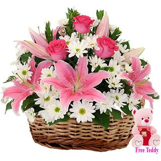 White Carnation and pink Liliums in basket with 6 inches teddy