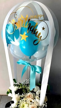 Small Blue and white balloons inside a trasparent balloon with 12 white flowers basket