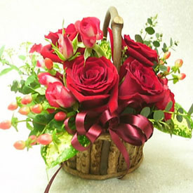 6 red roses in a small basket