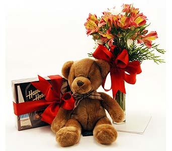 Teddy bear and chocolate box with a bunch of orange flowers