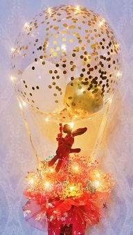 Golden confetti inside the transparent balloon tied to a box with 8 ferrero rocher chocolates in red net with illuminating fairy string lights