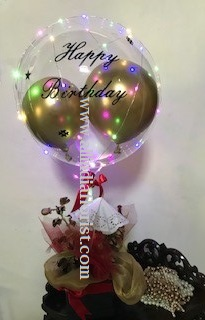 Print on balloon with happy birthday with led string fairy lights in a black box with dry flowers golden and red net and 5 red rose
