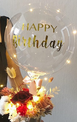 Happy birthday print on the transparent balloon with string lights and 12 flowers in a box