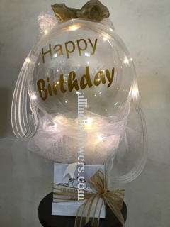 Happy birthday print on the transparent balloon white net wrapping and gold bow in a box and LED lights